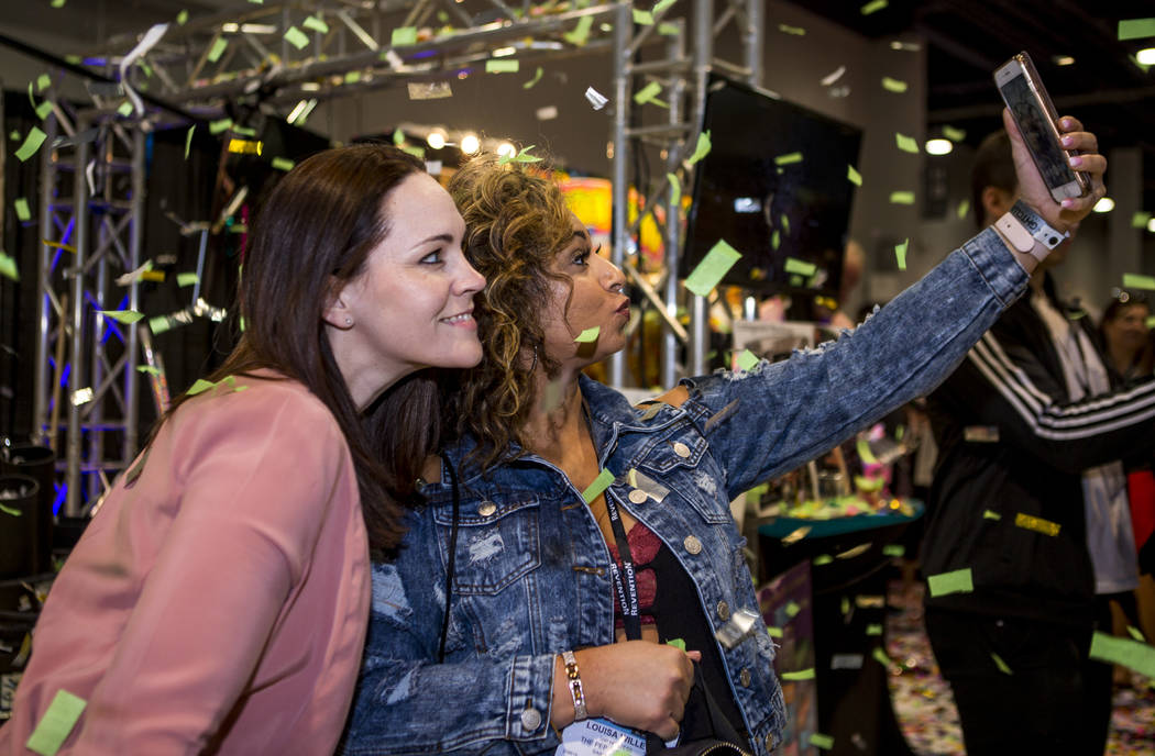 St. Louis residents Louisa Willey, right, and Gina McGirr take a selfie together as confetti from Flutter Fetti flies during the Nightclub and Bar Show at the Las Vegas Convention Center on Tuesda ...