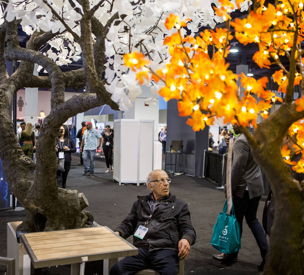 Valencia, Calif., resident Yeghia Harutunian of Arclite Inc. sits beneath light up trees from Arclite Inc. during the Nightclub and Bar Show at the Las Vegas Convention Center on Tuesday, March 27 ...