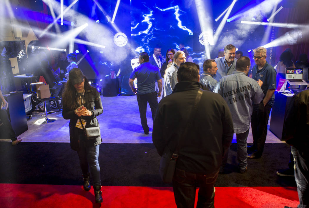 Attendees walk by a booth from ADJ lighting equipment during the Nightclub and Bar Show at the Las Vegas Convention Center on Tuesday, March 27, 2018.  Patrick Connolly Las Vegas Review-Journal @P ...