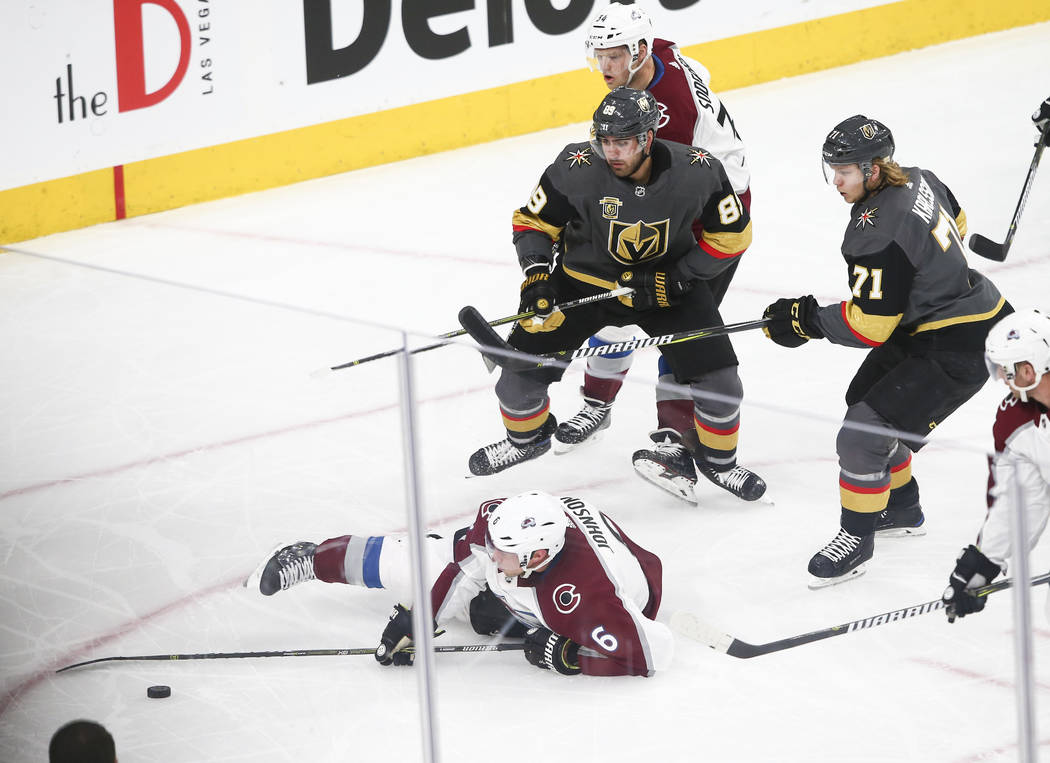 Colorado Avalanche defenseman Erik Johnson (6) falls to the ice in front ofr Golden Knights center William Karlsson (71) and right wing Alex Tuch (89) during the first period of an NHL hockey game ...