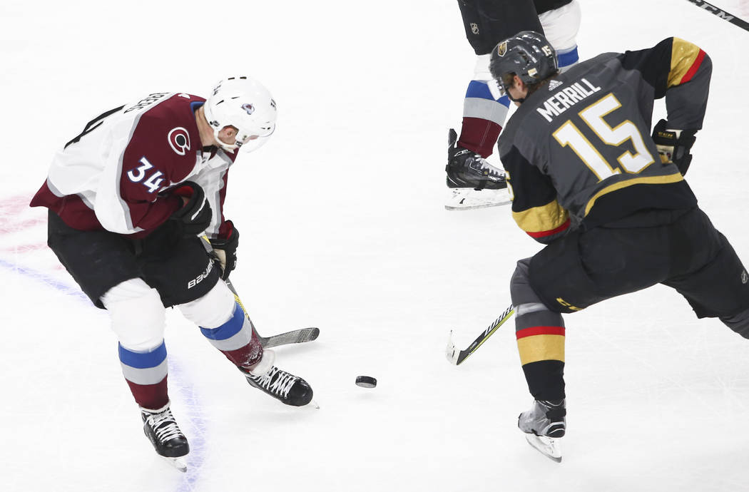 Colorado Avalanche center Carl Soderberg (34) and Golden Knights defenseman Jon Merrill (15) battle for the puck during the first period of an NHL hockey game at T-Mobile Arena in Las Vegas on Mon ...