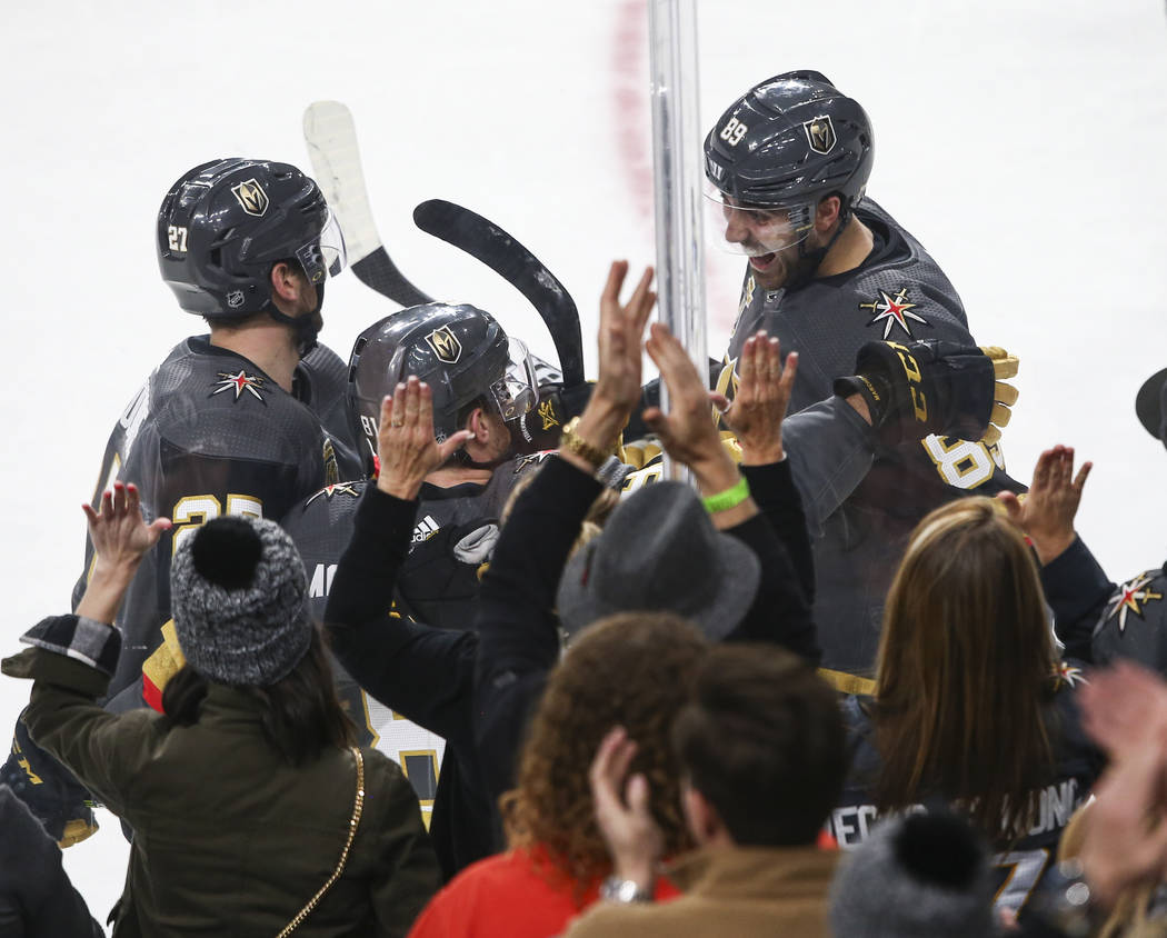 Golden Knights defenseman Shea Theodore (27) and right wing Alex Tuch (89) celebrate a goal by center Jonathan Marchessault (81) during the second period of an NHL hockey game against the Colorado ...