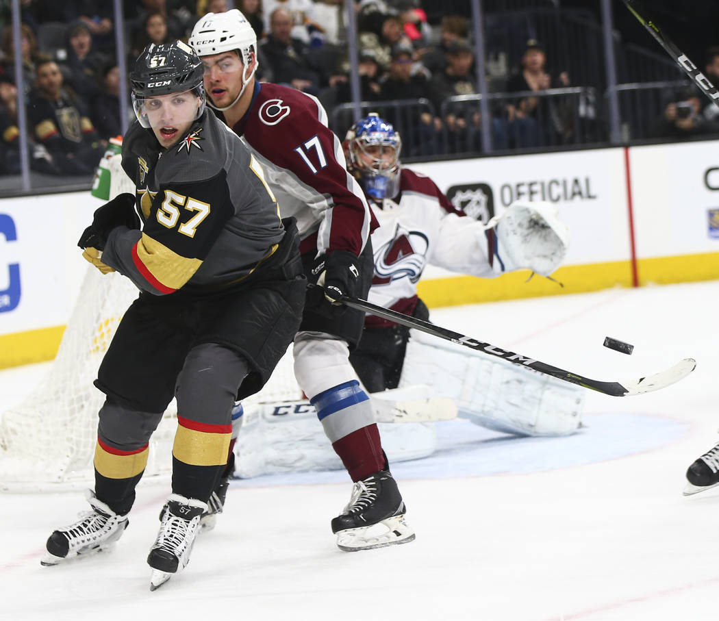Golden Knights left wing David Perron (57) eyes the puck as it flys by while Colorado Avalanche center Tyson Jost (17) defends during the third period of an NHL hockey game at T-Mobile Arena in La ...