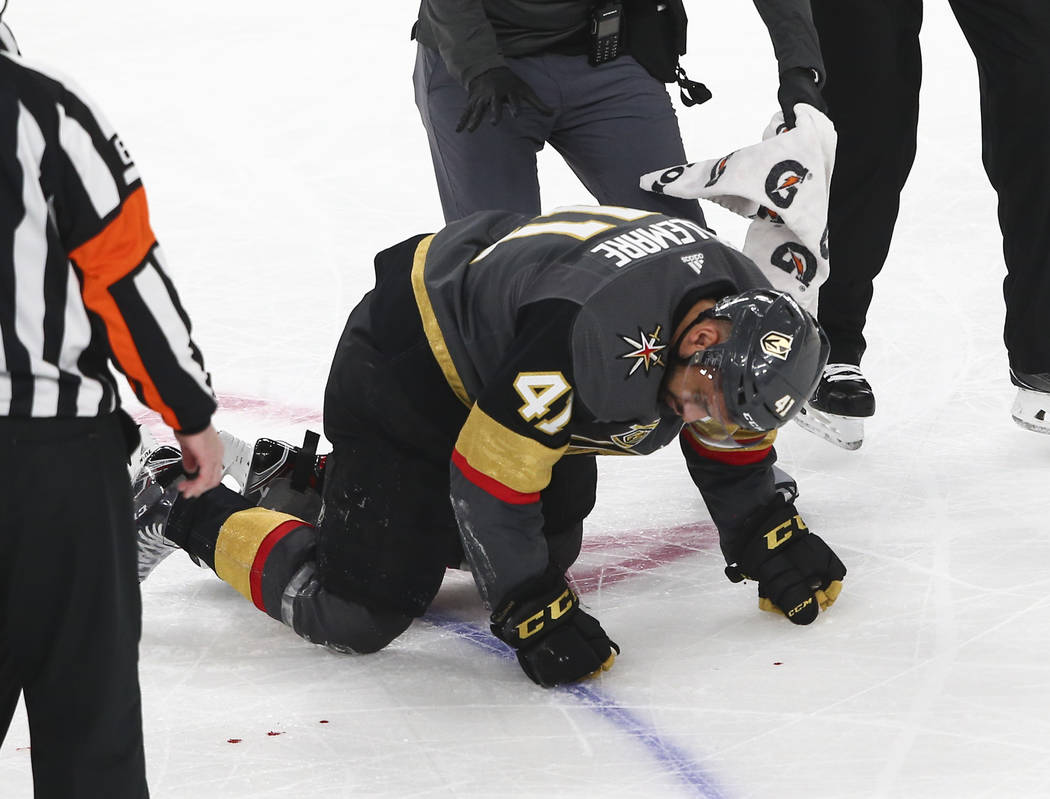 Golden Knights left wing Pierre-Edouard Bellemare (41) crawls on the ice after getting injured by a Colorado Avalanche player during the second period of an NHL hockey game at T-Mobile Arena in La ...