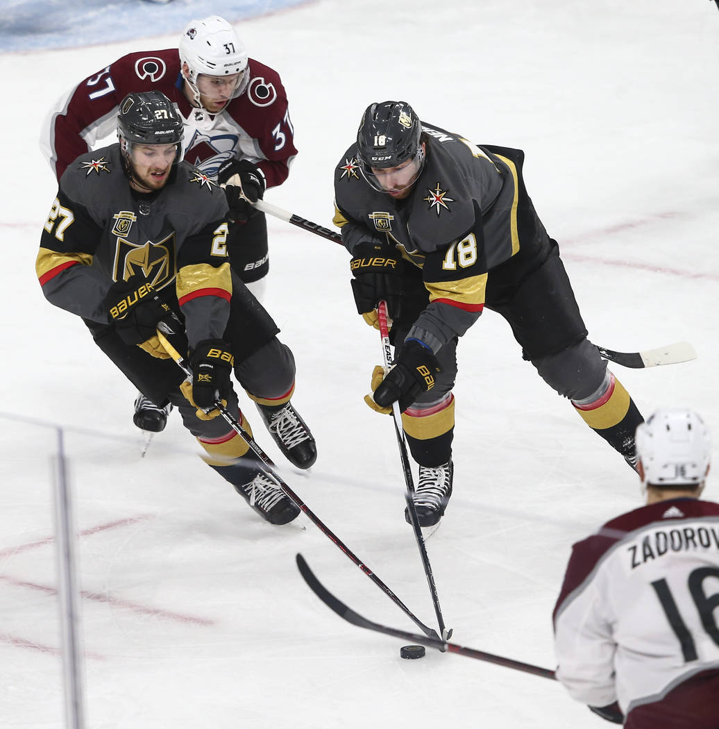 Golden Knights defenseman Shea Theodore (27) and left wing James Neal (18) move the puck as Colorado Avalanche left wing J.T. Compher (37) defends during the second period of an NHL hockey game at ...