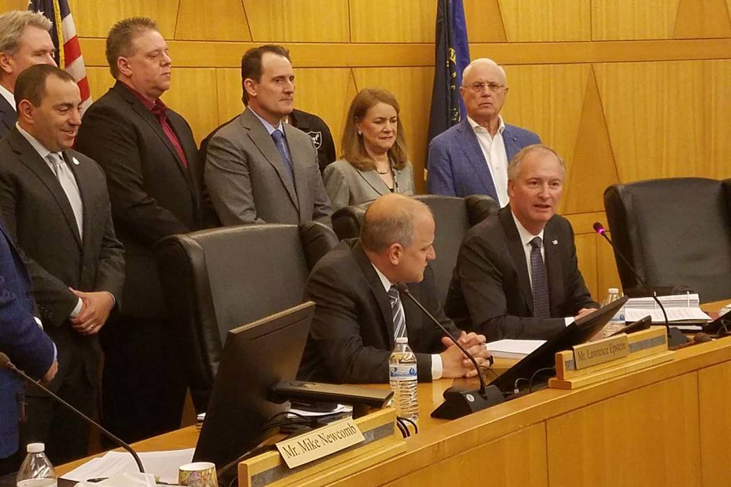 Steve Hill, seated right, speaks before signing the stadium development and lease agreements for the Las Vegas Stadium with Raiders President Marc Badain, seated left, at the Clark County Commissi ...