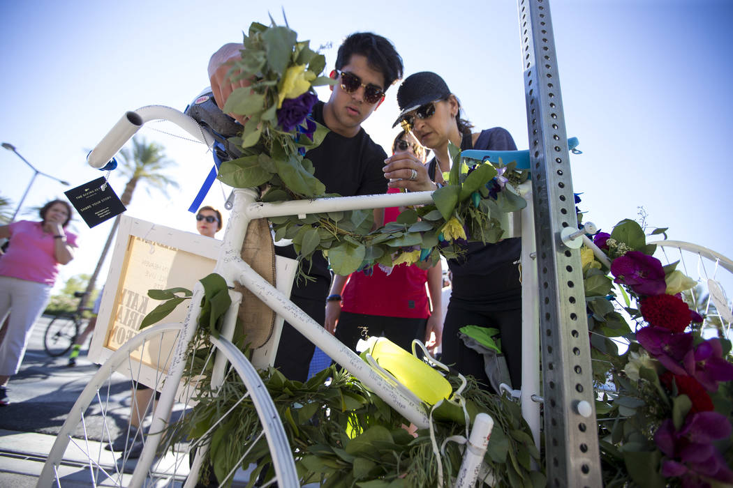 Dr. Kayvan Khiabani's widow Katy Barin, right, and her son Aria Khiabani, 16, leave a wreath on the ghost bike of Khiabani during a memorial service at the corner South Pavillion Center Drive near ...