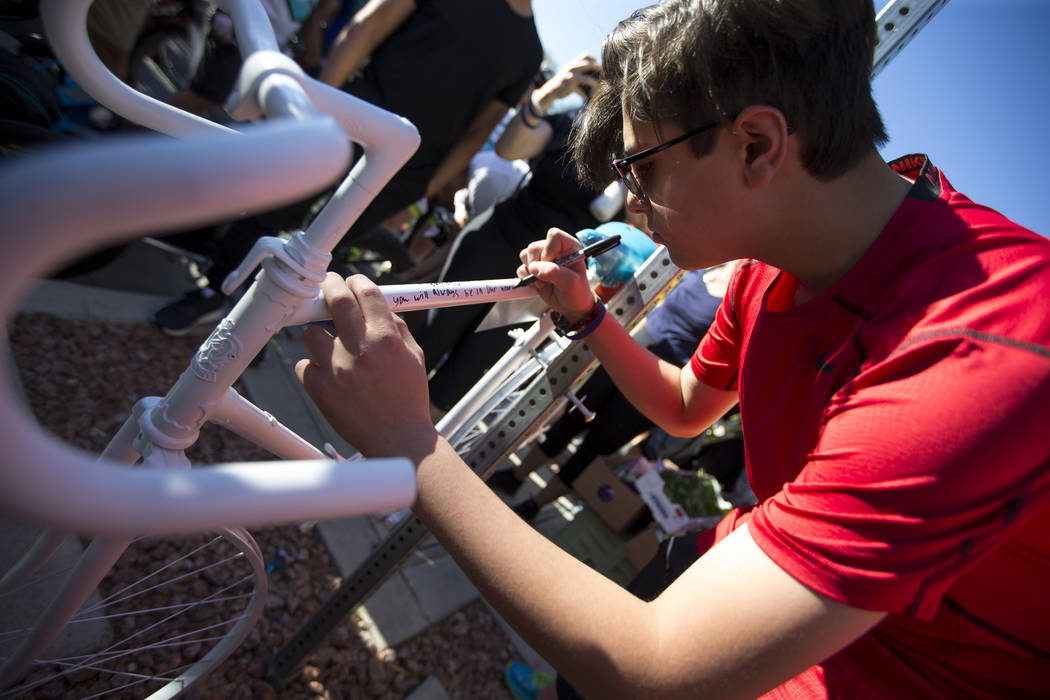 Dr. Kayvan Khiabani's son Keon Khiabani, 14, writes a message on the ghost bike of  Khiabani during a memorial service at the corner South Pavillion Center Drive near West Charleston Boulevard on  ...