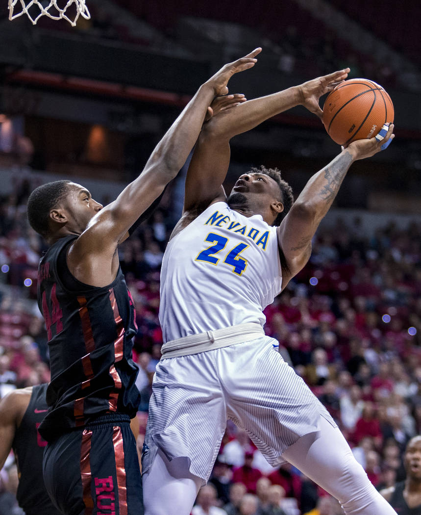 Nevada guard Jordan Caroline (24) jumps up for a shot attempt with UNLV forward Brandon McCoy (44) on his arm during the second half of an NCAA college basketball quarterfinals game in the Mountai ...