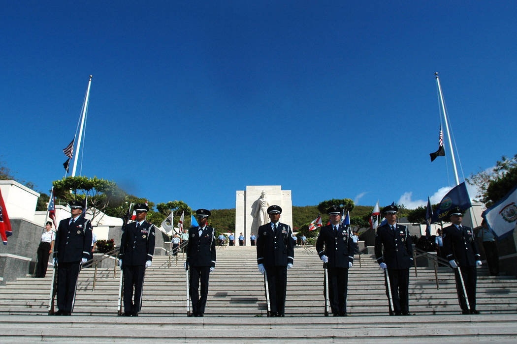 Members of the Hawaii honor guard stand at attention on the steps of the National Memorial Cemetery of the Pacific at Punchbowl crater before an early morning ceremony for Memorial Day in Honolulu ...