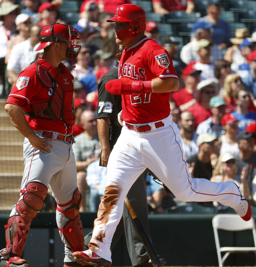 Los Angles Angels' Mike Trout, right, scores on an RBI-double by Albert Pujols as Cincinnati Reds catcher Devin Mesoraco looks away during the first inning of a spring training baseball game Monda ...