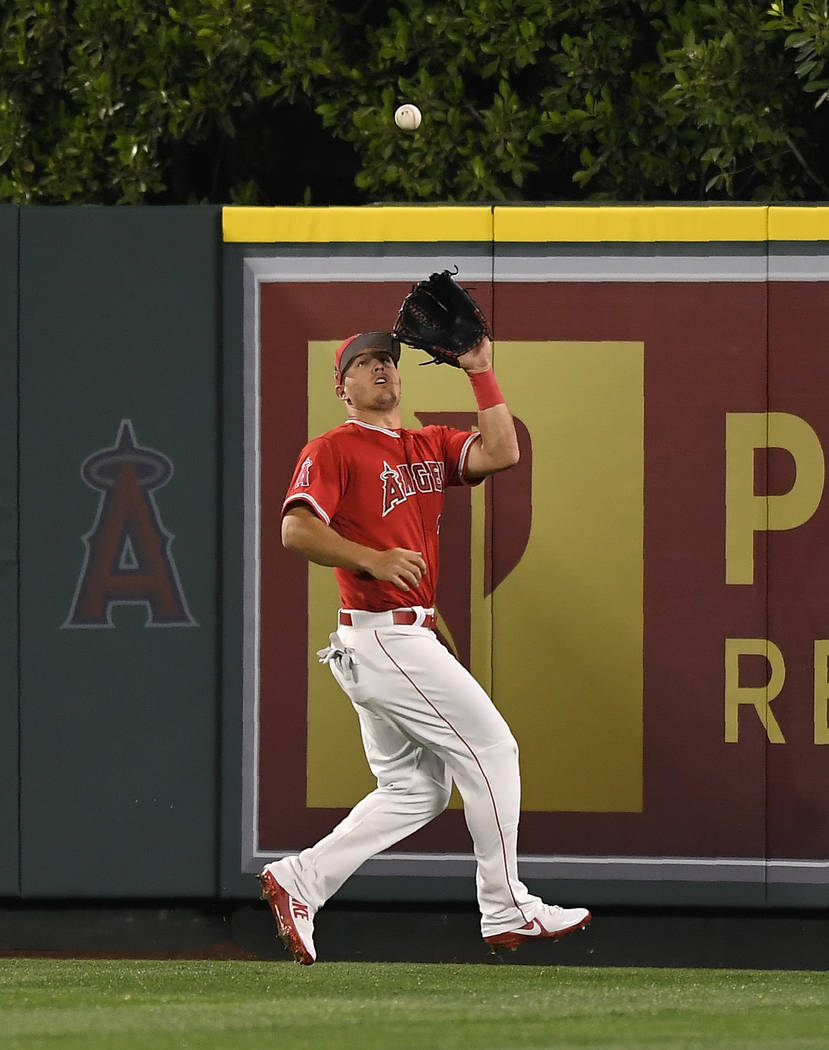 Los Angeles Angels center fielder Mike Trout makes a catch on a ball hit by Los Angeles Dodgers' Joc Pederson during the sixth inning of a spring training baseball game Sunday, March 25, 2018, in  ...