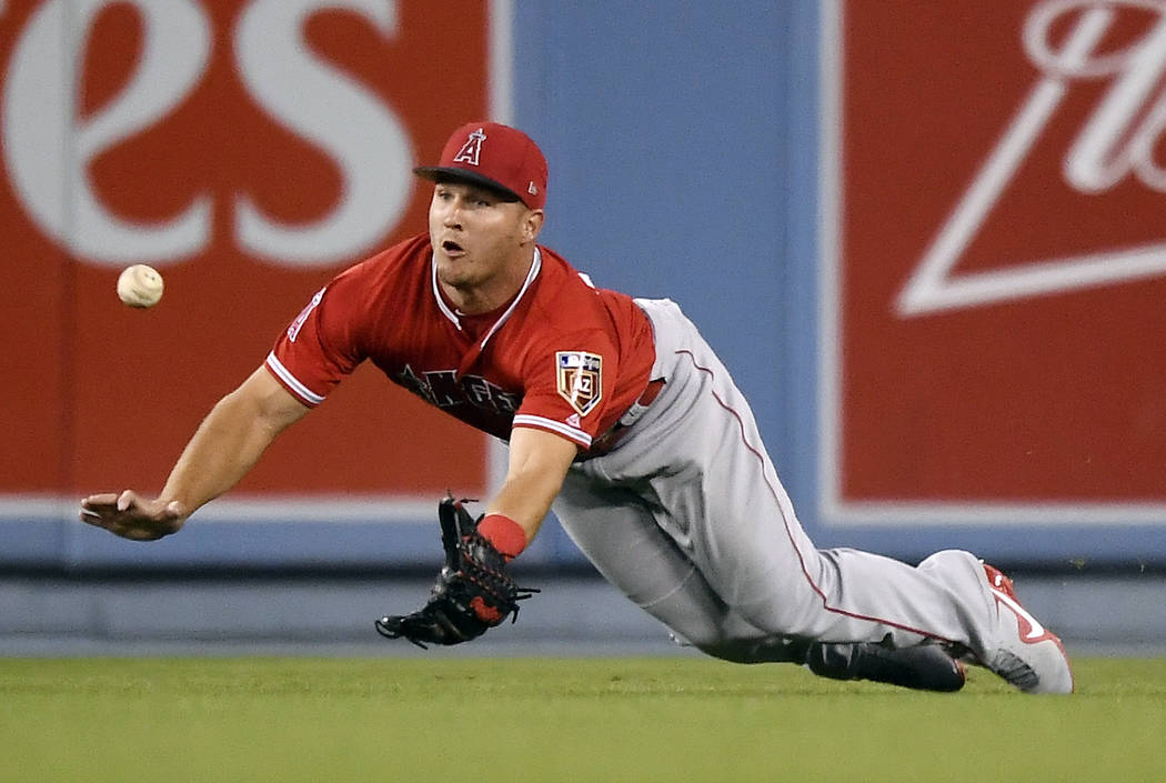 Los Angeles Angels center fielder Mike Trout makes a catch on a ball hit by Los Angeles Dodgers' Chris Taylor during the first inning of a preseason baseball game Monday, March 26, 2018, in Los An ...