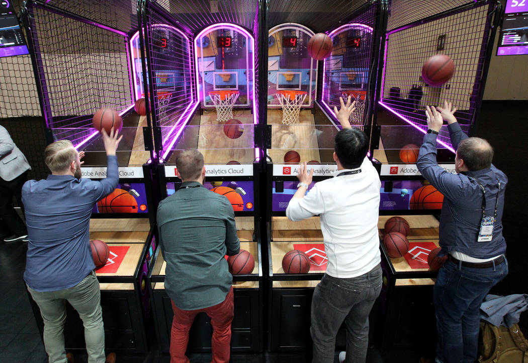 Adobe Summit trade show attendees, from left, Scott Lowry, Nate Wilcox, Chris Zheng and Geoff Thorne compete during the March Madness #HackTheBracket application at the Sands Convention Center in  ...