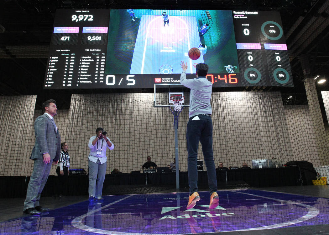 Russell Bennett of London shoots a basket at the Adobe Summit trade show during the March Madness #HackTheBracket application at the Sands Convention Center in Las Vegas Tuesday, March 27, 2018. K ...