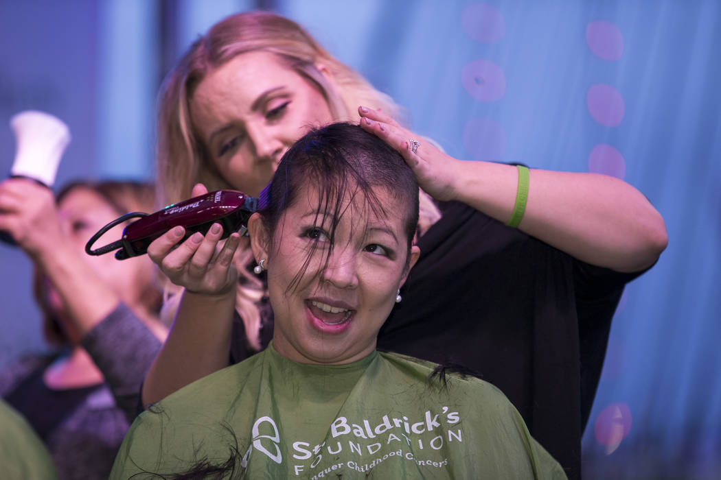 Cancer survivor and Las Vegas local Lisa King, 33, shaves her head during a St. Baldrick's head-shaving event to raise money for childhood cancer research outside the New York-New York on the Las  ...