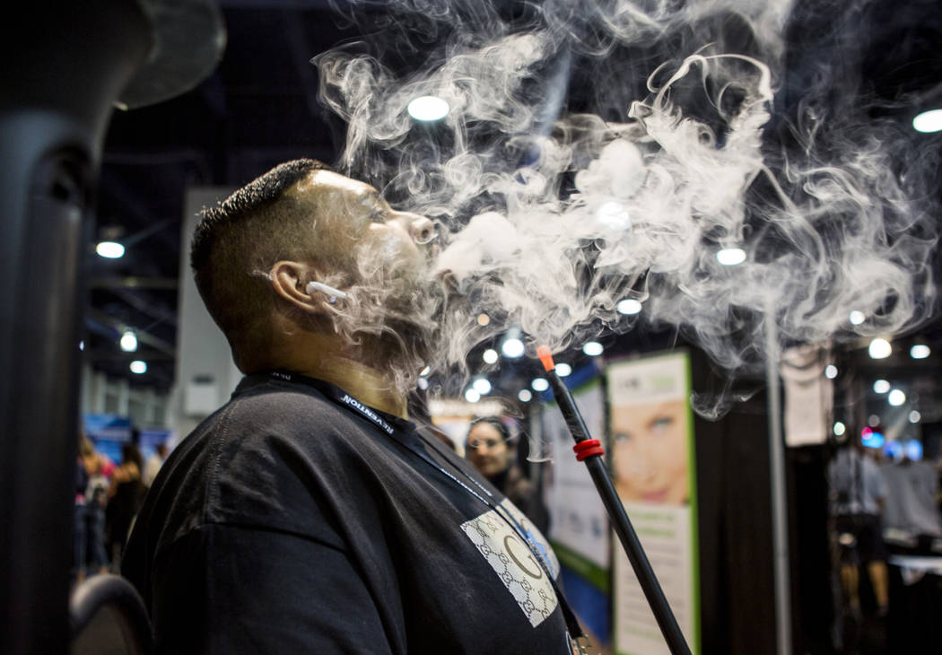 Sunny Patel, owner of Xhale Bar and Lounge near Lake Tahoe, tries out an electronic hookah rig from O2 Hookah during the Nightclub and Bar Show at the Las Vegas Convention Center on Tuesday, March ...