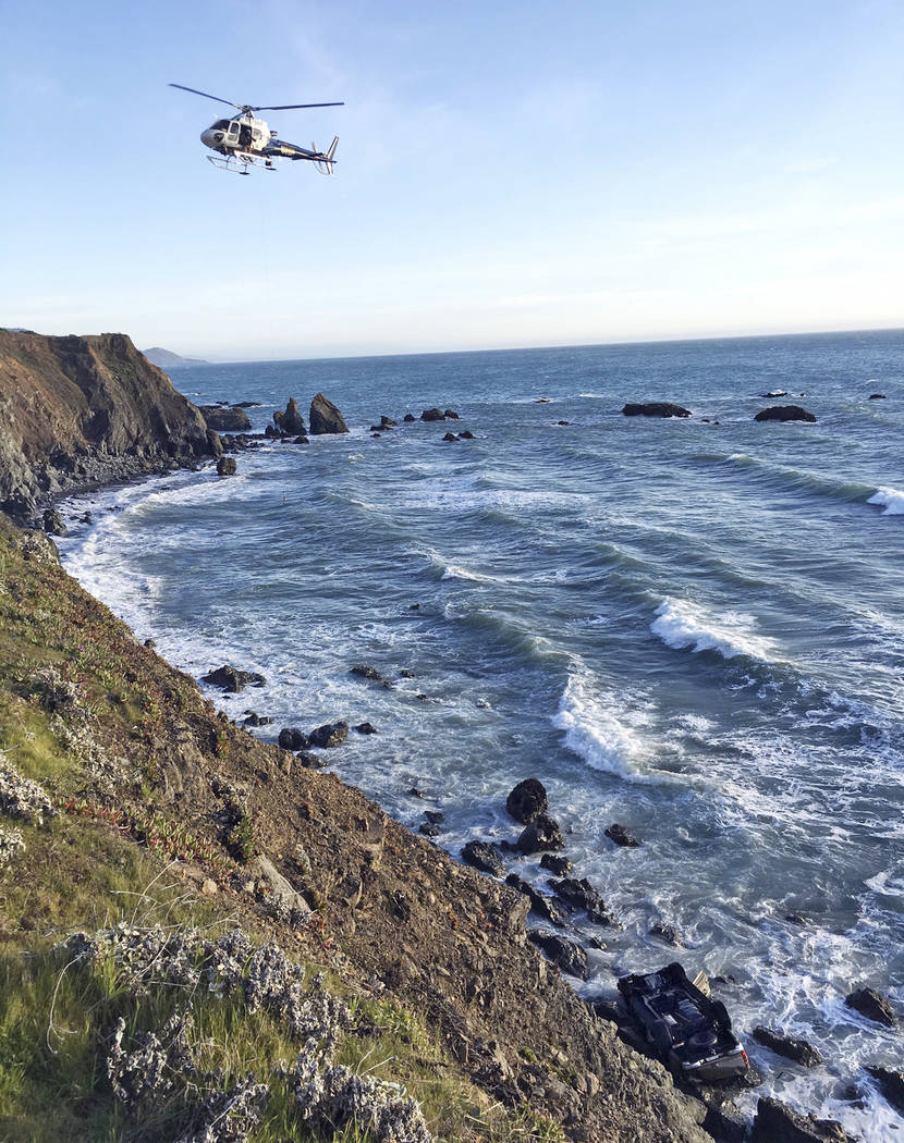 This photo provided by the California Highway Patrol shows a helicopter hovering over steep coastal cliffs Tuesday, March 27, 2018, near Mendocino, Calif., where a vehicle, visible at lower right, ...