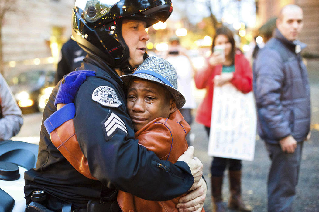 Portland police Sgt. Bret Barnum, left, and Devonte Hart, 12, hug at a 2014 rally in Portland, Ore., where people had gathered in support of the protests in Ferguson, Mo. (Johnny Huu Nguyen via AP ...