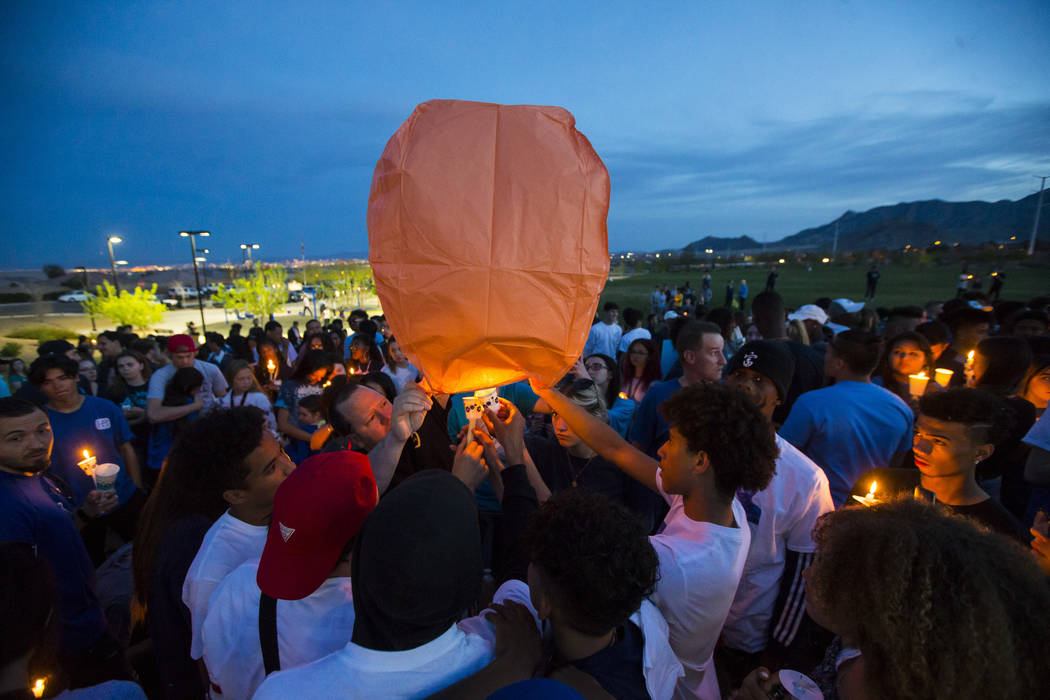 """Attendees light a balloon during a candlelight vigil at Knickerbocker Park in Las Vegas Friday, March 30, 2018 for Centennial High School students Albert """"A.J."""" Rossi, Dylan Mack and Bro ..."""