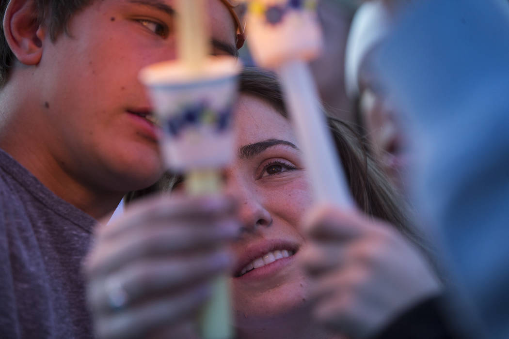"Allie Rossi, center, is comforted by Brennan Mecke while mourning the loss of her brother, Albert ""A.J."" Rossi, during a candlelight vigil at Knickerbocker Park in Las Vegas Friday, Marc ..."