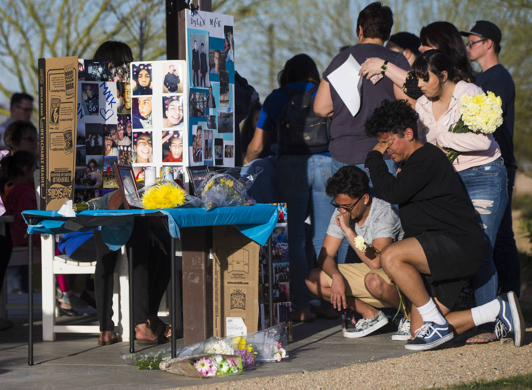 "Jesus Vargas, far right, mourns during a candlelight vigil at Knickerbocker Park in Las Vegas Friday, March 30, 2018. Centennial High School students Albert ""A.J."" Rossi, Dylan Mack and  ..."