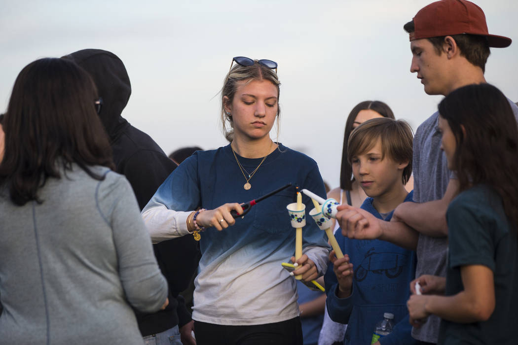 Attendees light candles during a candlelight vigil at Knickerbocker Park in Las Vegas Friday, March 30, 2018 for Centennial High School students Albert ÒA.J.Ó Rossi, Dylan Mack and Brook ...