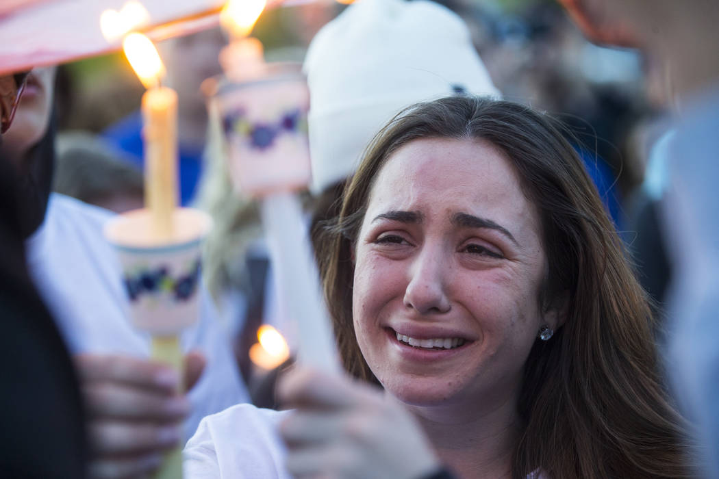 "Allie Rossi mourns the loss of her brother, Albert ""A.J."" Rossi, during a candlelight vigil at Knickerbocker Park in Las Vegas Friday, March 30, 2018. Albert ""A.J."" Rossi, alon ..."