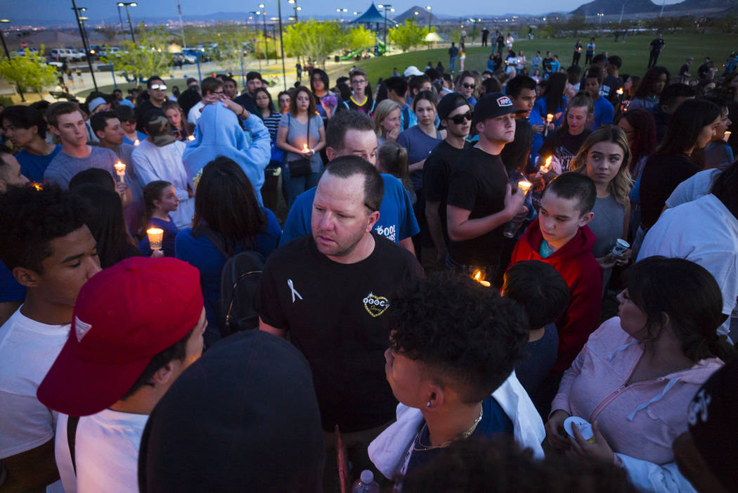 Morgan Mack, center, talks with friends and classmates of his son, Dylan Mack, during a candlelight vigil at Knickerbocker Park in Las Vegas Friday, March 30, 2018. Dylan Mack, along with fellow C ...
