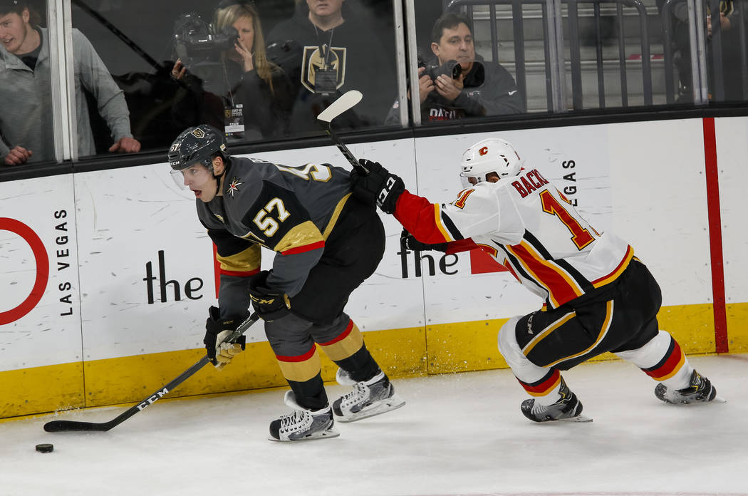 Vegas Golden Knights left wing David Perron (57) controls the puck as Calgary Flames center Mikael Backlund (11) follows behind during the second period of an NHL hockey game at the T-Mobile Arena ...