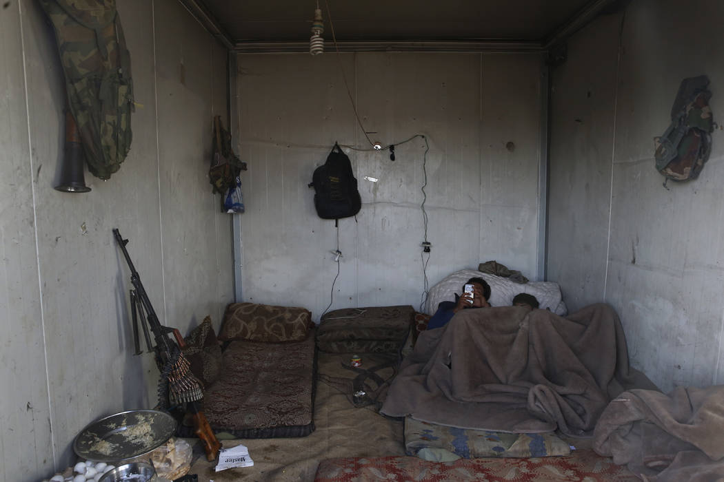 Fighters from the U.S-backed Syrian Manbij Military Council rest on their kiosk at a front line position against the Turkish-backed fighters at Halawanji village, north of Manbij town, Syria, Thur ...
