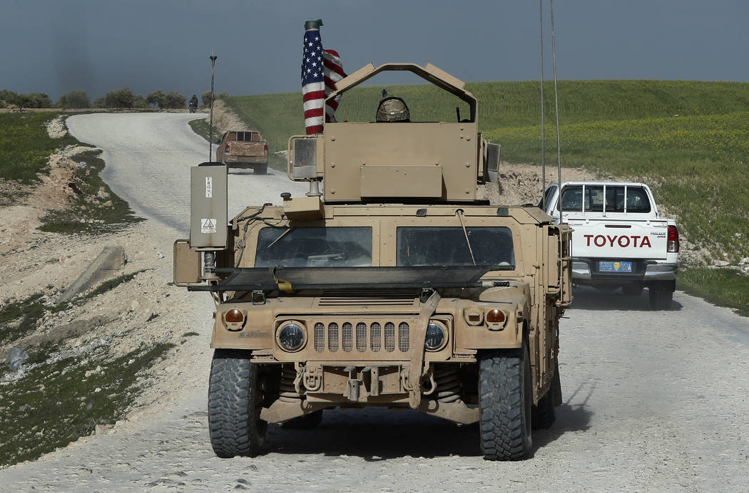 U.S. troop's humvee passes vehicles of fighters from the U.S-backed Syrian Manbij Military Council on a road leading to the tense front line with Turkish-backed fighters, at Halawanji village, nor ...