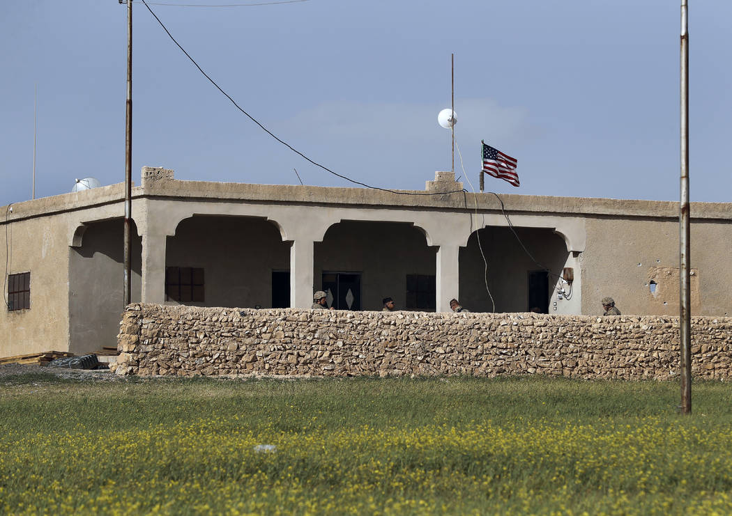 U.S. soldiers sit on a house that turned to an outpost on a road leading to the tense front line between U.S-backed Syrian Manbij Military Council fighters and Turkish-backed fighters, at Halawanj ...