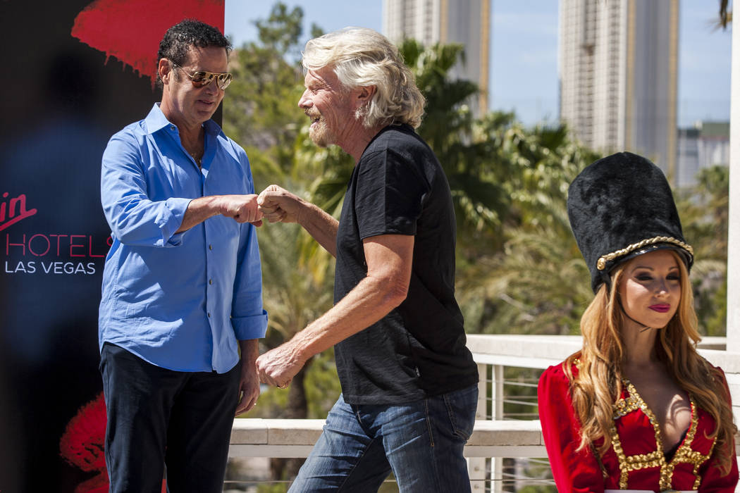 Virgin Group Founder Sir Richard Branson, center, fist bumps Virgin Hotels CEO Raul Leal, left, during a press conference at the Hard Rock Hotel in Las Vegas on Friday, March 30, 2018.  Patrick Co ...