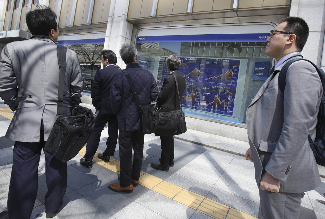 People look at an electronic stock board of a securities firm in Tokyo, Friday, March 30, 2018. Shares rose in Asia on Friday after technology and consumer-focused stocks led an overnight rally on ...