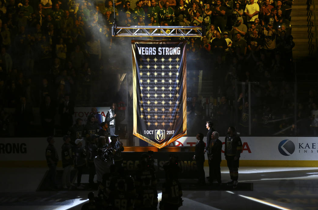 A banner is raised in honor of the victims of the shooting before the start of an NHL hockey game between the Golden Knights and the San Jose Sharks at T-Mobile Arena in Las Vegas on Saturday, Mar ...