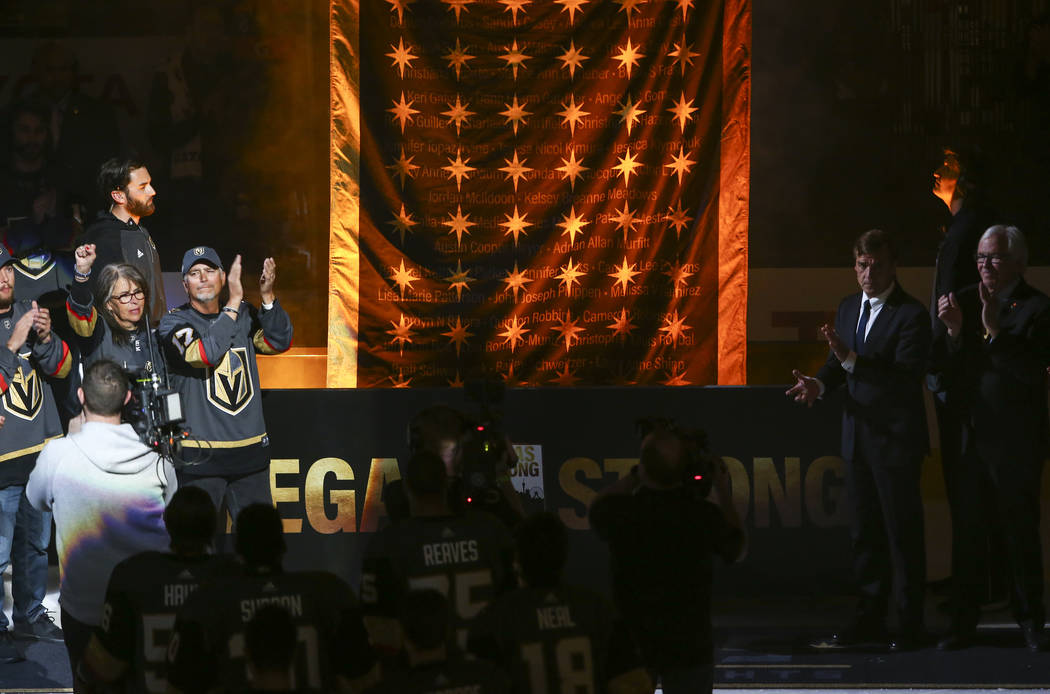 Chris and Debbie Davis, left, parents of Neysa Tonks, who was killed in the Oct. 1 shooting, cheer as a banner is raised in honor of the victims of the shooting before the start of an NHL hockey g ...