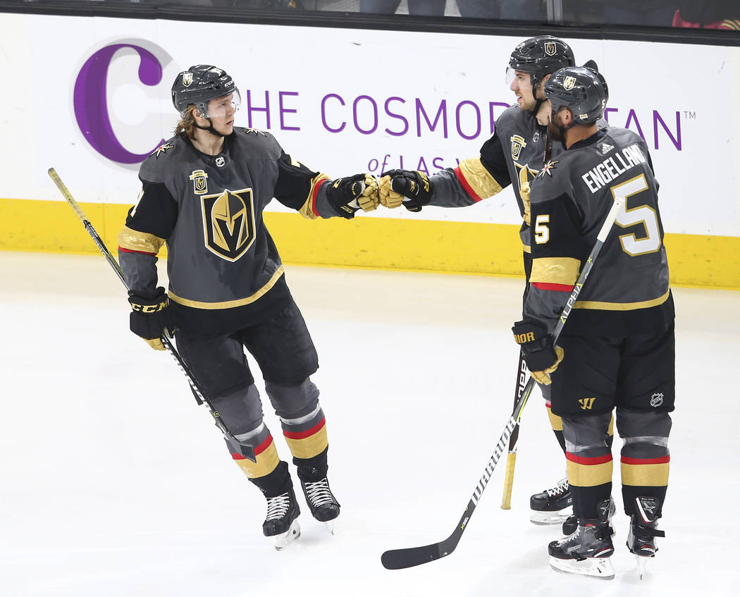 Golden Knights center William Karlsson, left, celebrates a goal by Golden Knights defenseman Shea Theodore (27) during the first period of an NHL hockey game against the San Jose Sharks at T-Mobil ...