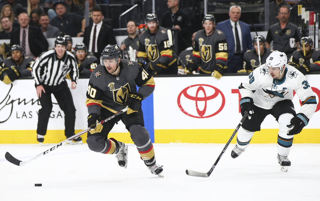 Golden Knights center Ryan Carpenter (40) skates with the puck as San Jose Sharks center Logan Couture (39) defends during the second period of an NHL hockey game at T-Mobile Arena in Las Vegas on ...