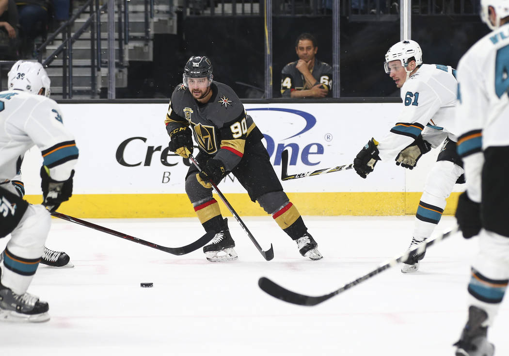 Golden Knights left wing Tomas Tatar (90) moves the puck between San Jose Sharks center Logan Couture (39) and defenseman Justin Braun (61) during the second period of an NHL hockey game at T-Mobi ...