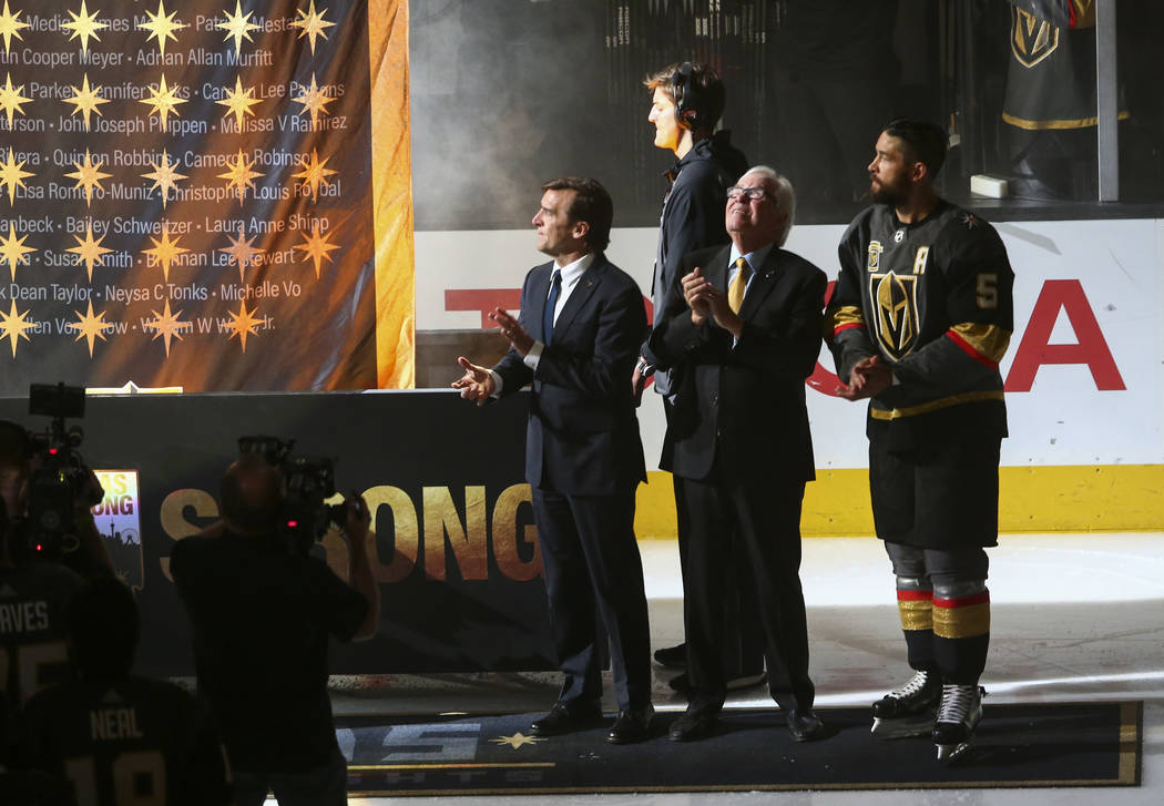 Golden Knights general manager George McPhee, from left, team owner Bill Foley and defenseman Deryk Engelland (5) watch as a banner is raised in honor of the victims of the Oct. 1 shooting before  ...