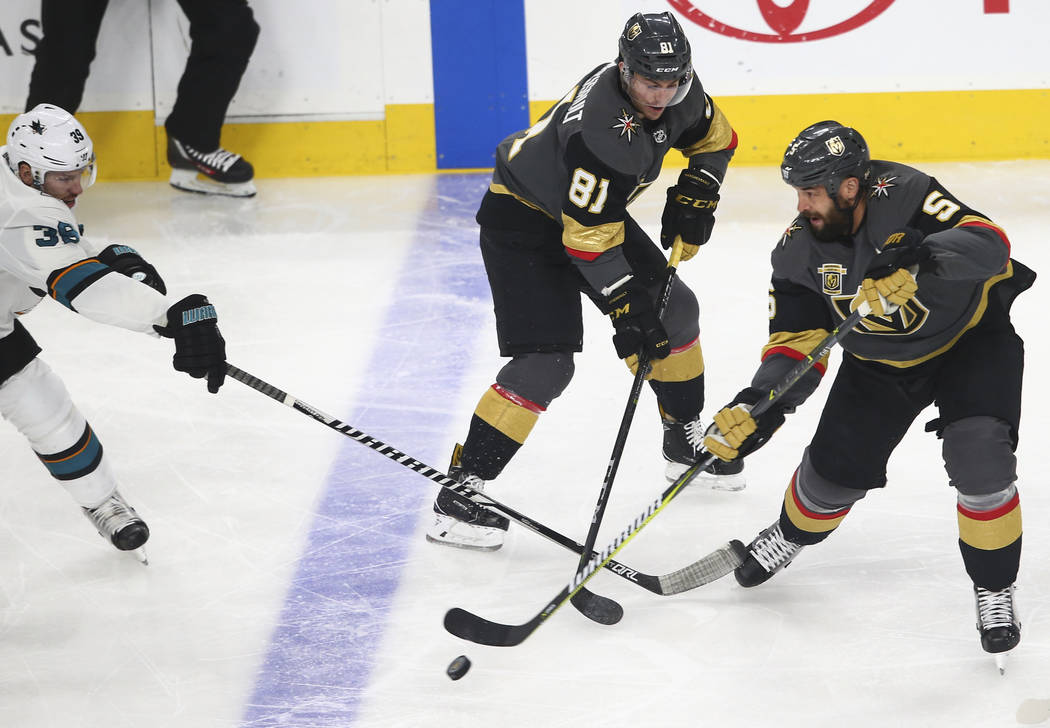 San Jose Sharks center Logan Couture (39) defends as Golden Knights defenseman Deryk Engelland (5) controls the puck while center Jonathan Marchessault (81) looks on during the first period of an  ...