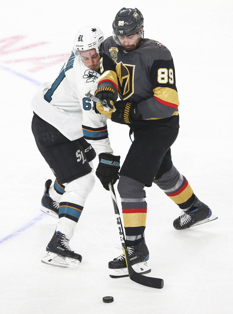 Golden Knights right wing Alex Tuch (89) and San Jose Sharks defenseman Justin Braun (61) battle for the puck during the second period of an NHL hockey game at T-Mobile Arena in Las Vegas on Satur ...