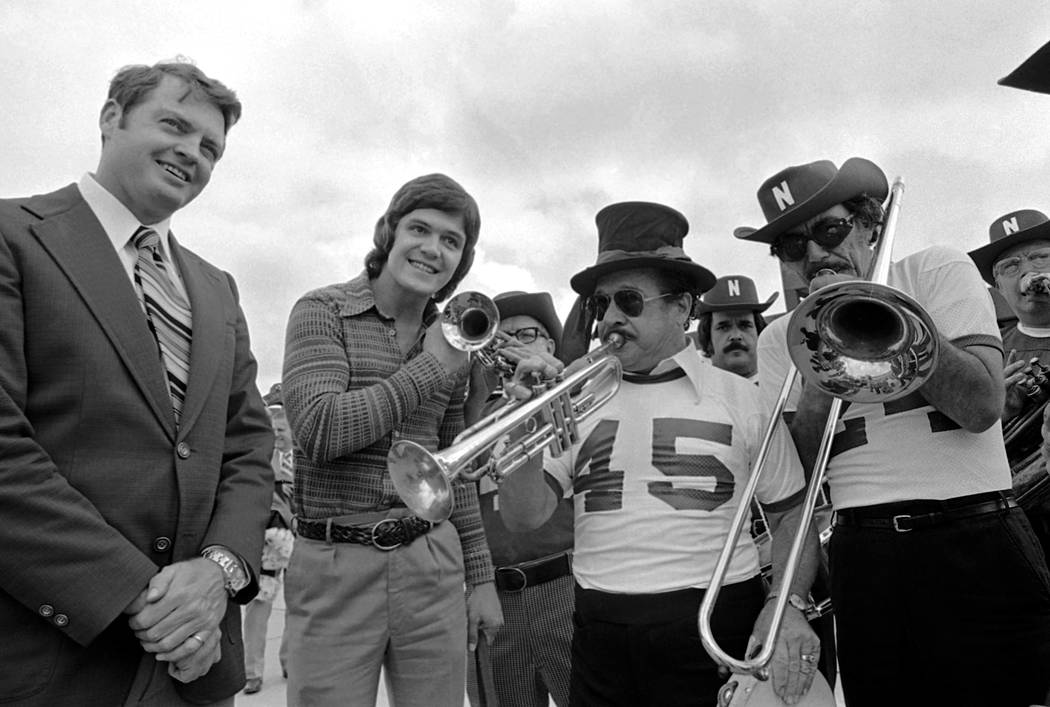 Nebraska quarterback Dave Humm is flanked by his head coach Tom Osborne as they listen to a dixieland jazz band greeting upon arrival in New Orleans on Tuesday, Dec. 24, 1974. The 8th ranked Cornb ...