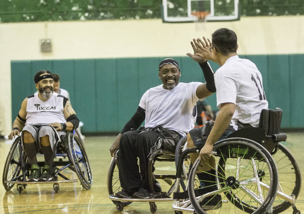 Larry Purfoy, middle, celebrates with Cesar Robledo during practice for the Las Vegas Yuccas of the National Wheelchair Basketball Association on Tuesday, January 16, 2018, at Rancho High School,  ...