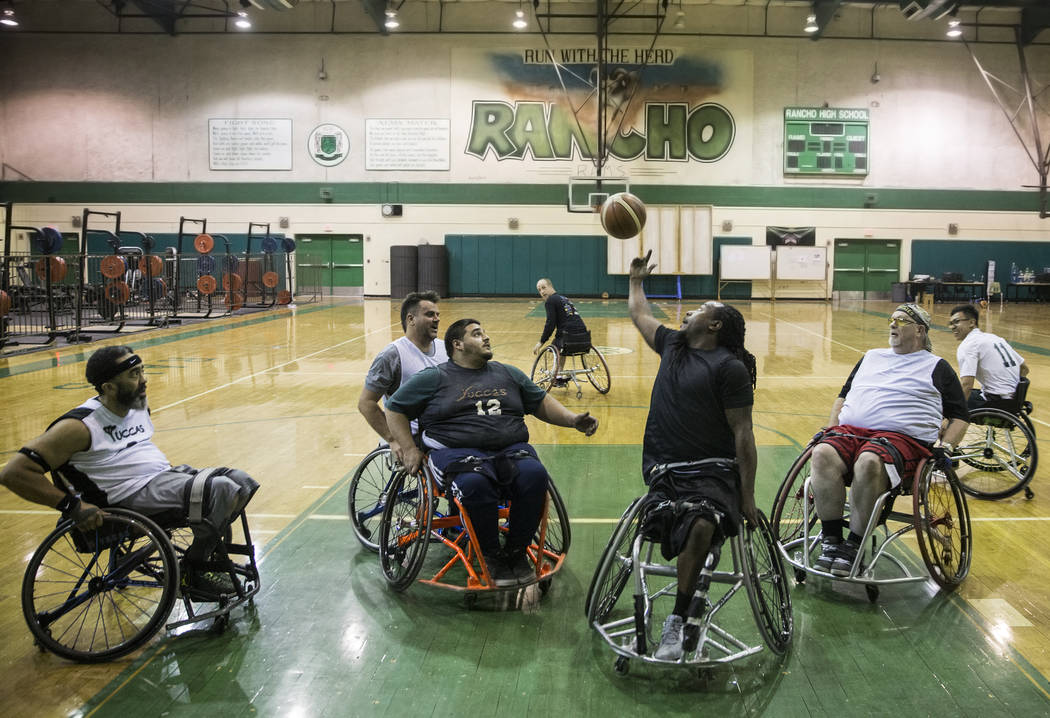 Marcus Hill, middle, grabs a rebound during practice for the Las Vegas Yuccas of the National Wheelchair Basketball Association on Tuesday, January 16, 2018, at Rancho High School, in Las Vegas. B ...
