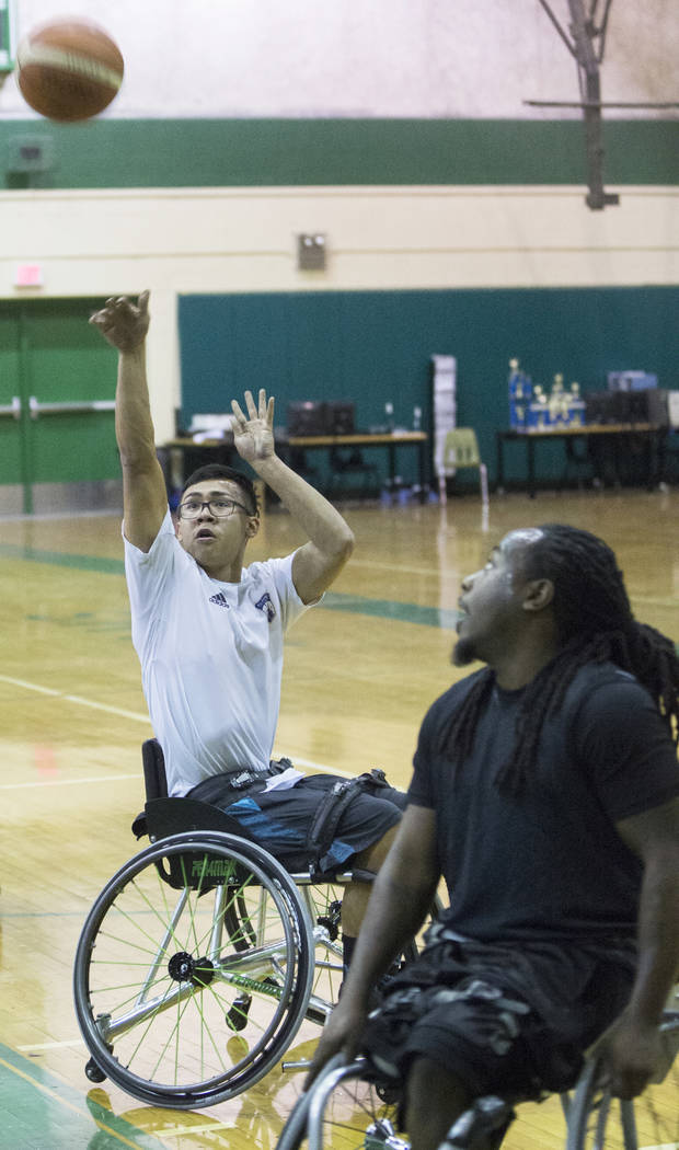 Cesar Robledo, left, shoots over Marcus Hill during practice for the Las Vegas Yuccas of the National Wheelchair Basketball Association on Tuesday, January 16, 2018, at Rancho High School, in Las  ...