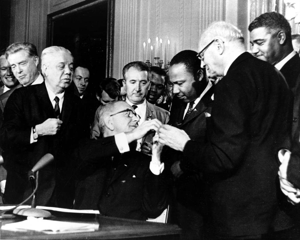 U.S. President Lyndon B. Johnson reaches to shake hands with Dr. Martin Luther King Jr. after presenting the civil rights leader with one of the 72 pens used to sign the Civil Rights Act of 1964 i ...