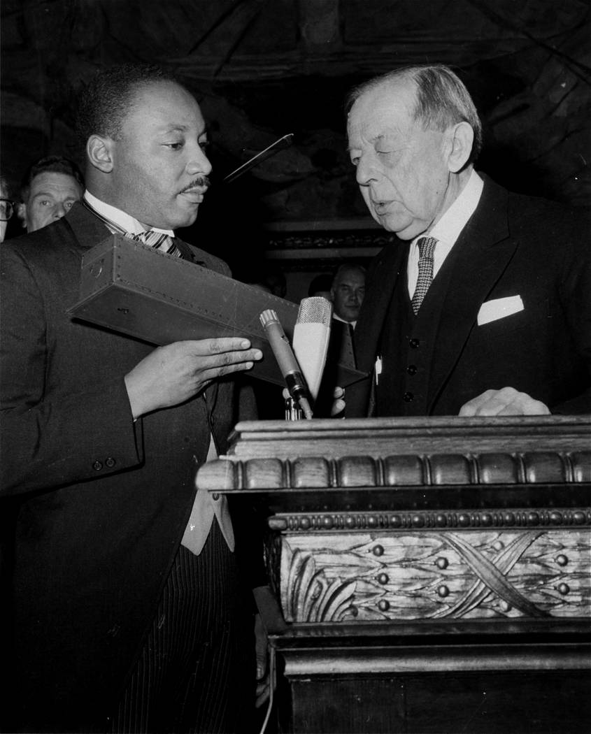 Dr. Martin Luther King, Jr., American civil rights leader, holds a case containing the Nobel Peace Prize gold medal after the presentation in Oslo, Norway, December 10, 1964.  Gunnar Jahn, chairma ...