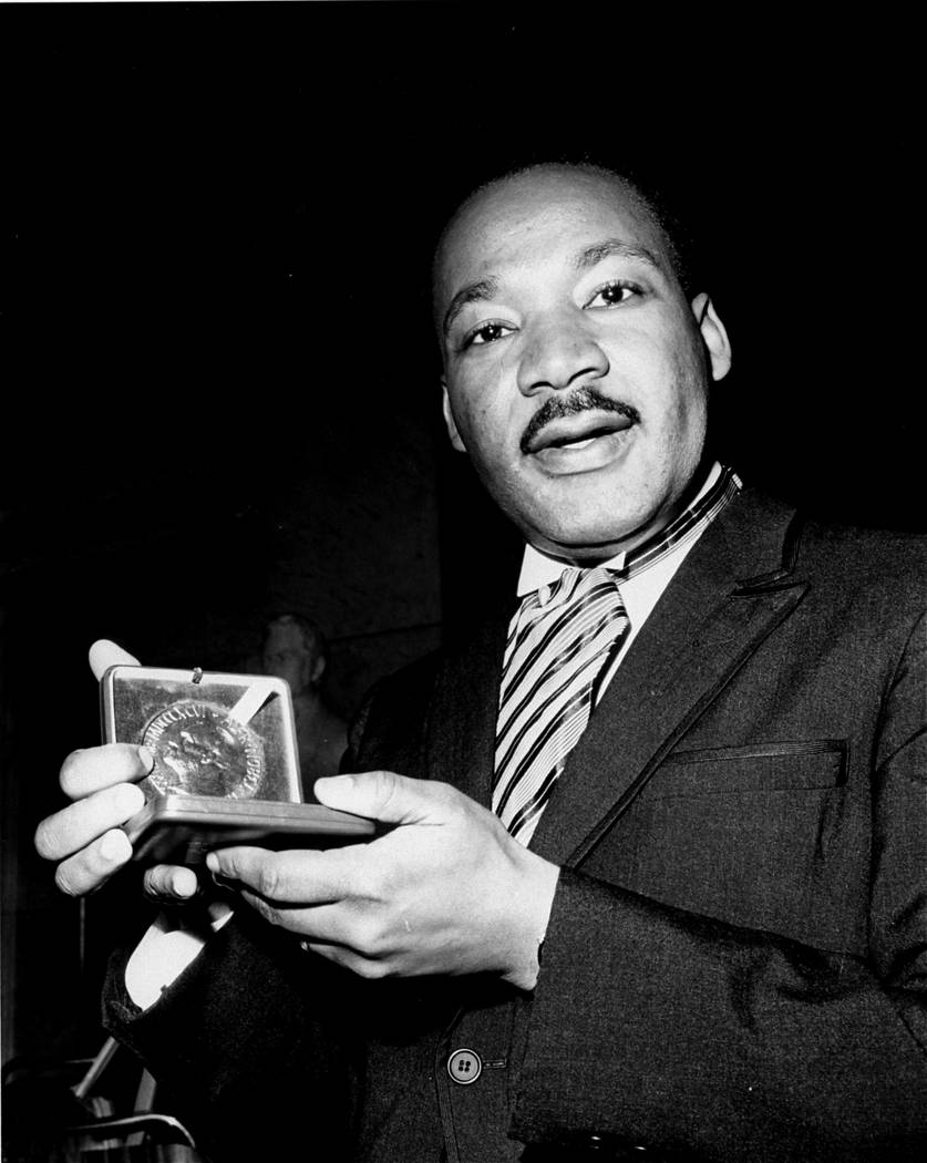 Dr. Martin Luther King, Jr. displays his 1964 Nobel Peace Prize medal in Oslo, Norway, December 10, 1964.  The 35-year-old Dr. King was honored for promoting the principle of non-violence in the c ...